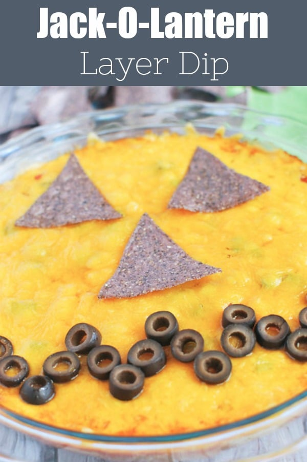 Jack-O-Lantern Layer Dip - how cute for a Halloween party! Layers of refried beans, guacamole, salsa, cheese, and green onions topped with tortilla chips and olives to look like a scary pumpkin!