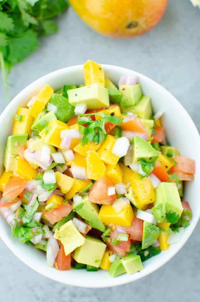 Overhead shot of chopped mango, avocado, tomatoes, red onion, jalapeno, and cilantro tossed in lime juice in a white bowl