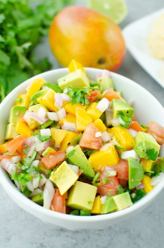 Chopped mango, avocado, tomatoes, red onion, jalapeno, and cilantro tossed in lime juice in a white bowl